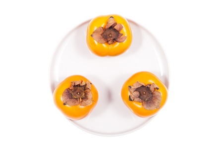 Fresh persimmon fruits on a white background photo