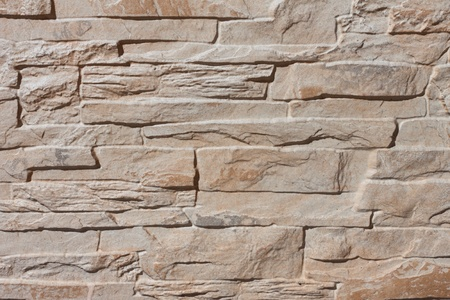 Sandy artificial stone wall background close up photo