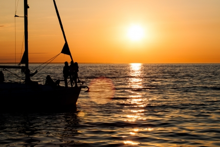 Sailing boat silhouette, sunset, ocean and one bird photo