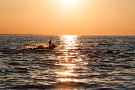 Young guy cruising in the baltic sea  on a jet ski during sunset photo