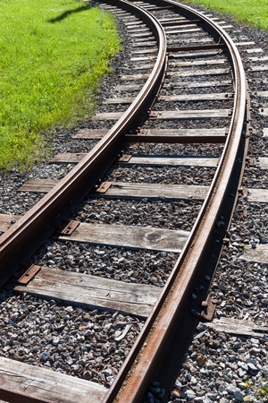 bullhead: Railway rail road track disappearing around a curve in grass
