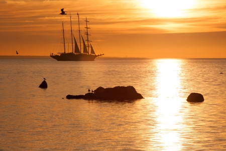 Old sail ship silhouette in sunset in sea photo