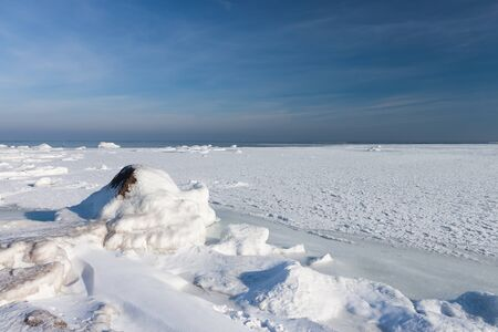 Frozen baltic sea with rock photo
