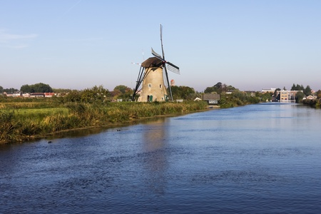 Holland windmill in Kinderdijk on the canal photo