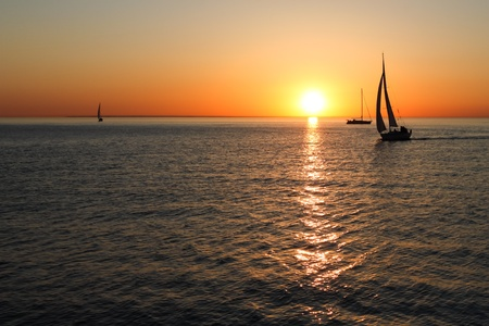 The gold silhouettes of boats at sea with sunset photo
