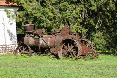 old tractor: Old rusty farming tractor near barn Stock Photo