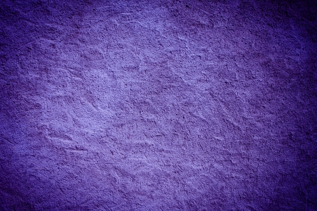 Vintage dark purple painted plaster concrete wall background. Dark edged photo