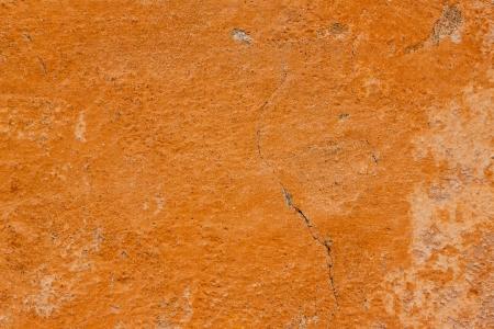 Cracked orange wall wallpaper background Stockfoto