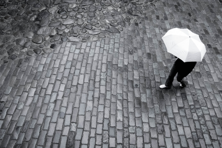 personas en la calle: Mujer con paraguas bajo la lluvia en la pavimentaci�n de camino de piedra Foto de archivo
