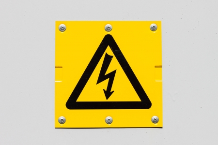 Sign of danger high voltage symbol on the white wall photo