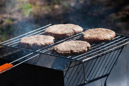 Four raw Hamburgers on Barbeque Grill with smoke photo
