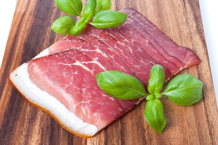 Pressed ham meat on wooden brown board with basil leafs photo