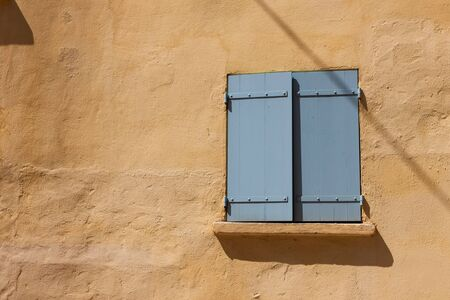 Old yellow wall with closed window photo