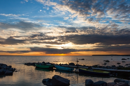 woody bay: Peaceful sunset with dramatic sky and boats Stock Photo