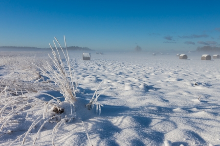 snowy hay bales with clouds near farm haouse Stock Photo - 16032792