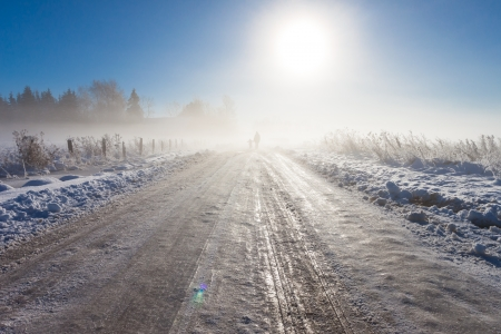 Mother and child on foggy snow road near farm Stock Photo - 16110953