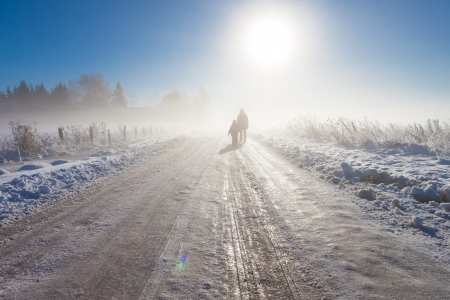 Mother and child on foggy snow road near farm and fence Stock Photo