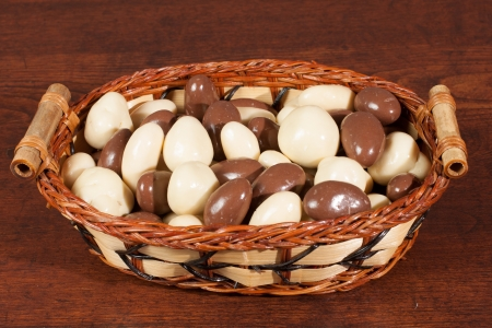 whisker: nuts in chocolate in whisker basket on wood Stock Photo