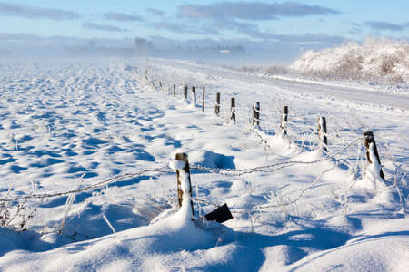 Barbed wire fence, road with snow covered ground and fog Stock Photo - 16582581