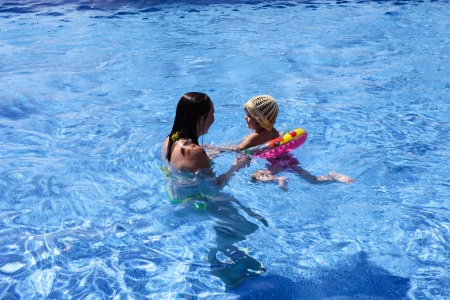 Mother teaching baby girl how to swim in a swimming pool.