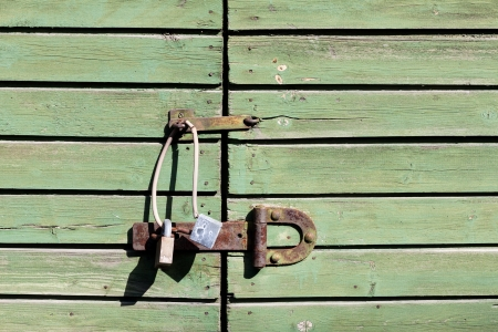 The padlock locking the wooden green door photo