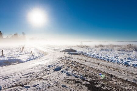 winter landscape at fog  with road near farm Stock Photo - 16984316