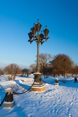 Antique frosty lamppost and beautiful snow covered branches against the azure sky photo