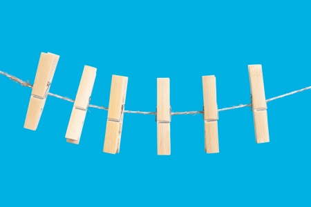 clothespins on rope isolated on blue background Stock Photo - 17670982