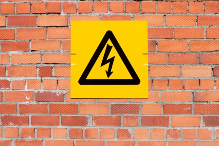 power failure: Yellow Danger of Death Warning sign on a brick wall Stock Photo