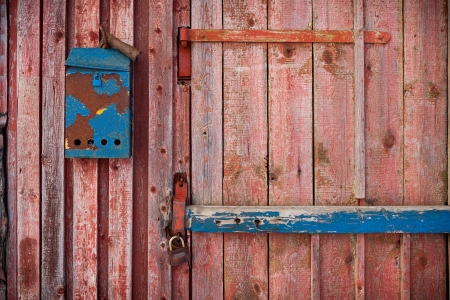 old mailboxe on an old wooden door painted red photo