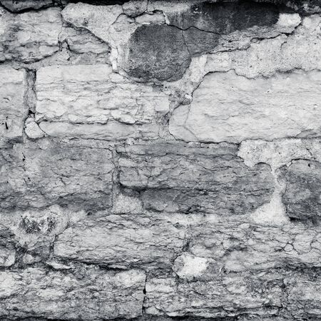 cracked plaster stone wall in black and white colors photo