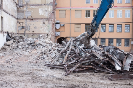 to thrash: Demolition truck in action  Heap of rubble and a demolished building in the background