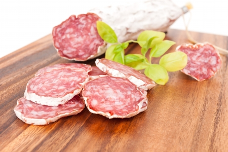 sliced salami on white background with basil leaves photo
