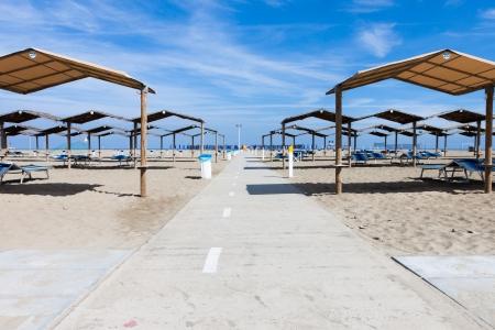 viareggio: Rows of the palm leaf sun shades on the beach in Italy
