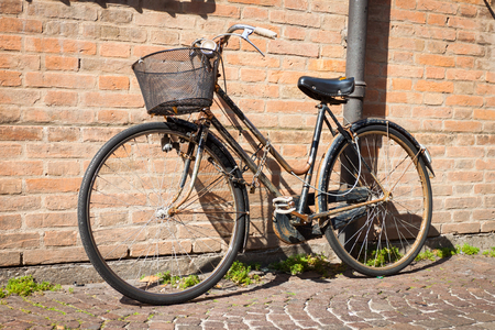 Italian old-style bicycles leaning against a wall in the historic centreof Ferrara photo