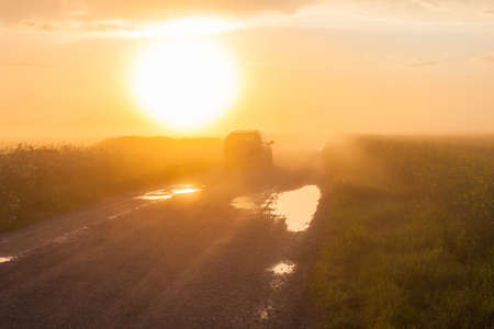 Car on rural road with fog and sunset photo