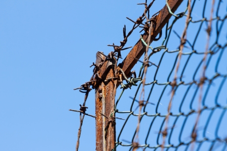 Rusty old fences of barb wire over blue sky photo