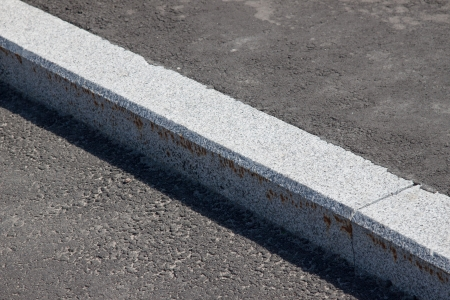 footpath: white curb stone border and asphalt road Stock Photo