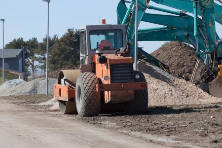 Excavators and asphalt compactor truck on construction site photo