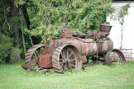 Old rusty farming tractor near barn photo