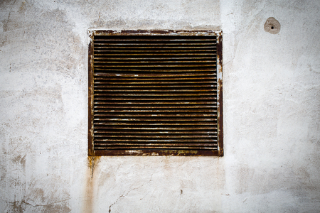 rustic air vent window on a grungy wall photo