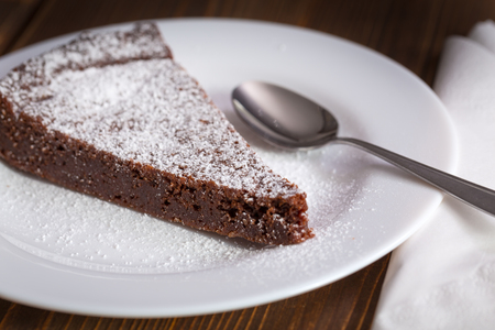 coffeetime: Chocolate Cake Slice on white dish and wooden background Stock Photo