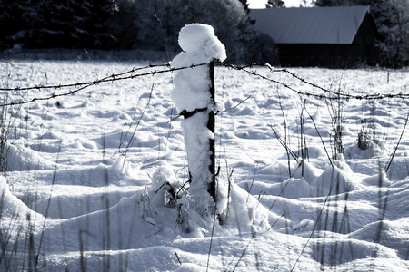 cloud drift: Barbed wire fence with snow