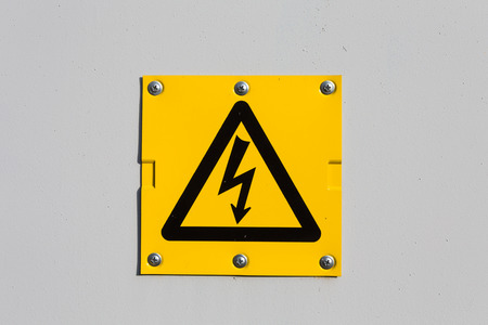 voltage symbol: Sign of danger high voltage symbol on the white wall