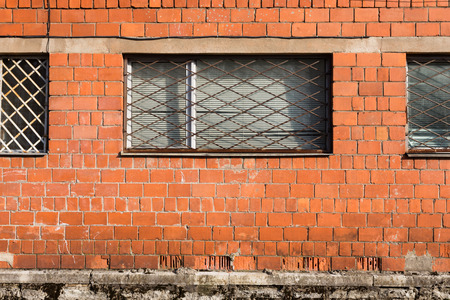 Red brick wall with metal window bars photo