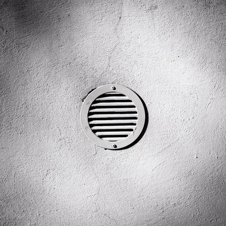 metal ventilation window on plaster wall background photo