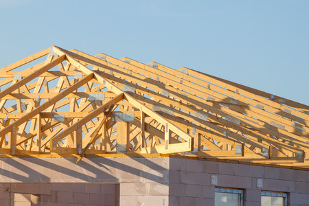 roof beam: New residential construction home framing over blue sky