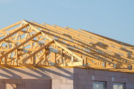 New residential construction home framing over blue sky