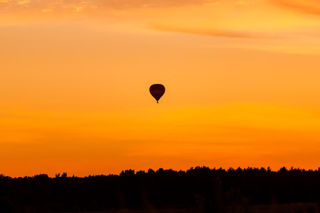 Hot air balloon flying at orange sunset sky