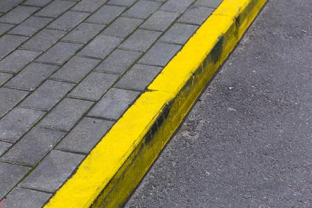 periphery: Yellow kerb line on the asphalt proad